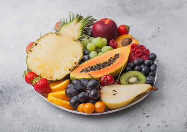 Verse rauwe biologische zomerbessen en exotisch fruit in witte plaat op lichte achtergrond. ananas, papaya, druiven, nectarine, sinaasappel, abrikoos, kiwi, peer, lychees, kers en physalis. bovenaanzicht
