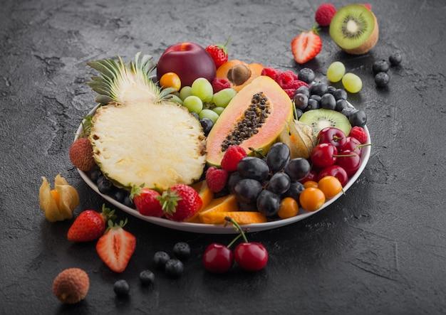 Verse rauwe biologische zomerbessen en exotisch fruit in witte plaat op zwarte achtergrond. ananas, papaya, druiven, nectarine, sinaasappel, abrikoos, kiwi, peer, lychees, kers en physalis. bovenaanzicht