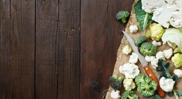 Verse rauwe bloemkool en broccoli op een oude houten tafelblad-weergave