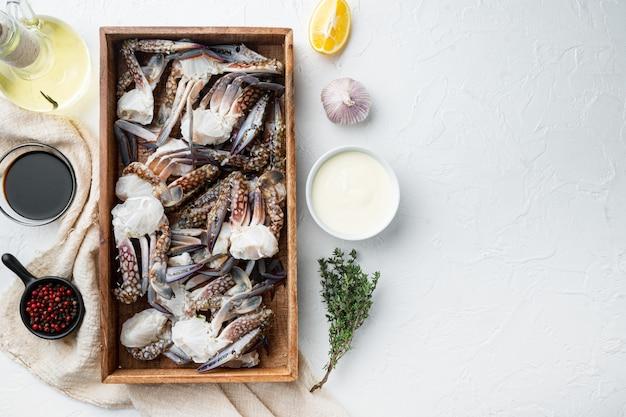 Verse rauwe blue swimming crab ocean gourme onderdelen set, in houten kist, op witte achtergrond, bovenaanzicht plat lag, met copyspace en ruimte voor tekst