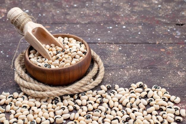 Verse rauwe bonen in bruine kom en verspreid over de bruine foto van rauwe bonen