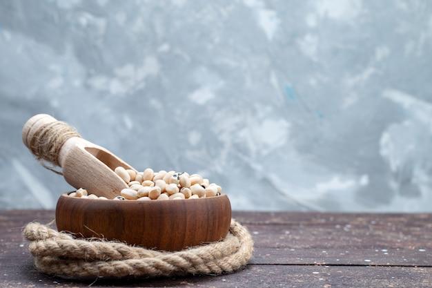Verse rauwe bonen in bruine kom op bruine rustieke houten, voedsel rauwe bonen haricot