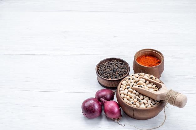 Verse rauwe bonen met kruiden en rode uien op licht