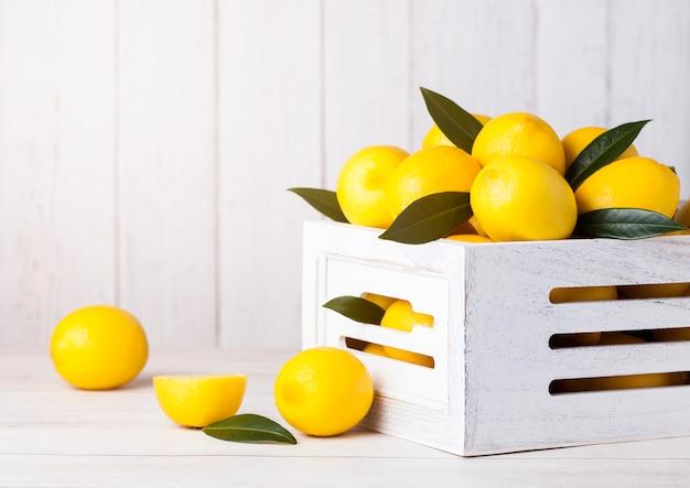 Verse rauwe citroenen in witte houten doos met bladeren