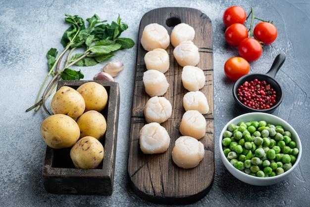 Verse rauwe coquilles ingrediënten klaar om te koken, op een grijze achtergrond