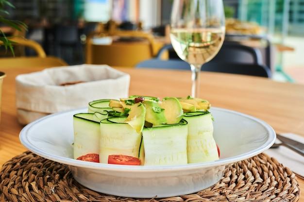 Verse rauwe courgettesalade met tomaten en avocado vergezeld van een glas witte wijn en een stoffen mand met brood met een ongericht restaurant interieur achtergrond