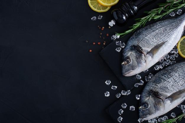 Verse rauwe doradavissen op donkere achtergrond met rozemarijn, citroen en andere kruiden.