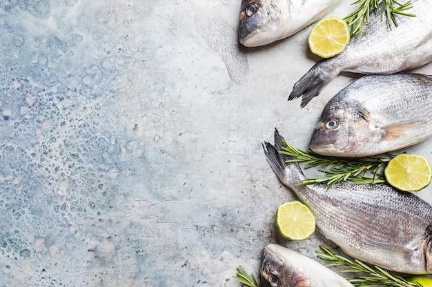 Verse rauwe dorado of zeebrasem met specerijen, kruiden, citroen en zout op blauwe achtergrond bovenaanzicht