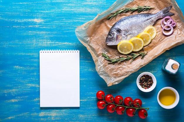 Verse rauwe dorado-vis op kookpapier met een notitieboekje voor recept bovenaanzicht op een blauwe achtergrond