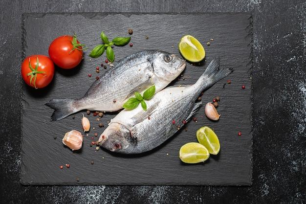 Verse rauwe dorado vis op zwarte stenen bord met kruiden, specerijen en groenten.