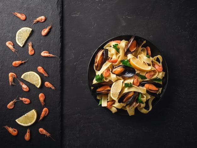 Verse rauwe garnalen of gekookte rode garnalen met kruiden en citroen op leisteen op donkere stenen achtergrond