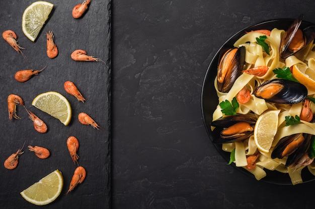 Verse rauwe garnalen of gekookte rode garnalen met specerijen en citroen op leisteen op donkere stenen achtergrond. zeevruchten, bovenaanzicht, plat leggen, ruimte kopiëren.