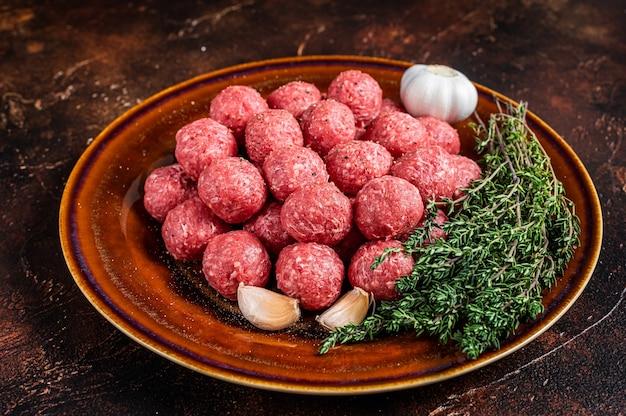 Verse rauwe gehaktballen van gehakt rundvlees en varkensvlees met tijm. donkere achtergrond. bovenaanzicht.