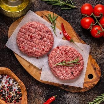 Verse rauwe gehakte zelfgemaakte grill beef hamburgers op houten snijplank, bovenaanzicht