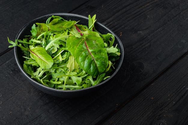 Verse rauwe gemengde greens rucola raab, mangold, snijbiet set, op zwarte houten tafel achtergrond, met kopie ruimte voor tekst