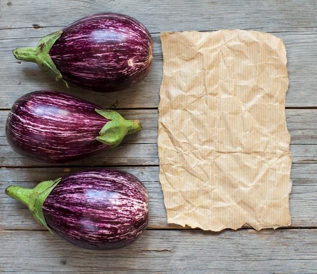 Verse rauwe gestreepte aubergines en ambachtelijk papier op houten bovenaanzicht