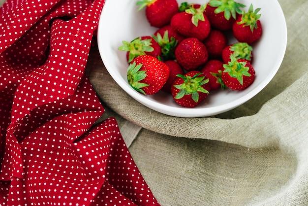 Verse rauwe gezonde voeding aardbeien fruit in plaat, geïsoleerd op wit, bovenaanzicht, flatlay close-up, copyspace voor tekst, frame. dorp rustieke canvas, platteland eten