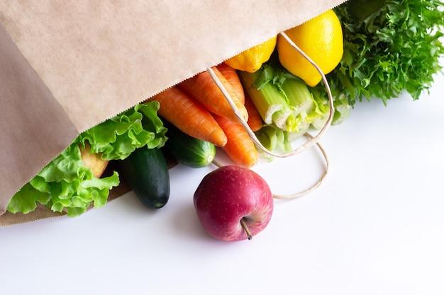 Verse rauwe groenten en fruit in een milieuvriendelijke papieren zak geïsoleerd op een witte muur