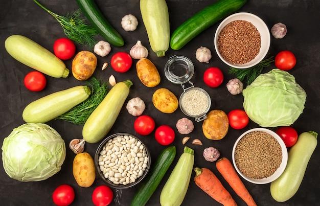 Verse rauwe groenten in assortiment op zwarte achtergrond in plat leggen. vegetarisch concept