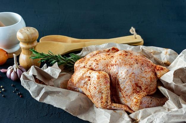 Verse rauwe kip op bakpapier en kruiden om te koken.