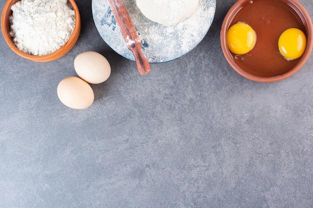 Verse rauwe kippeneieren met bloem op stenen tafel.