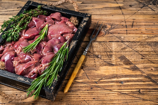 Verse rauwe kippenlever slachtafvallen vlees in een houten dienblad. houten achtergrond. bovenaanzicht. ruimte kopiëren.