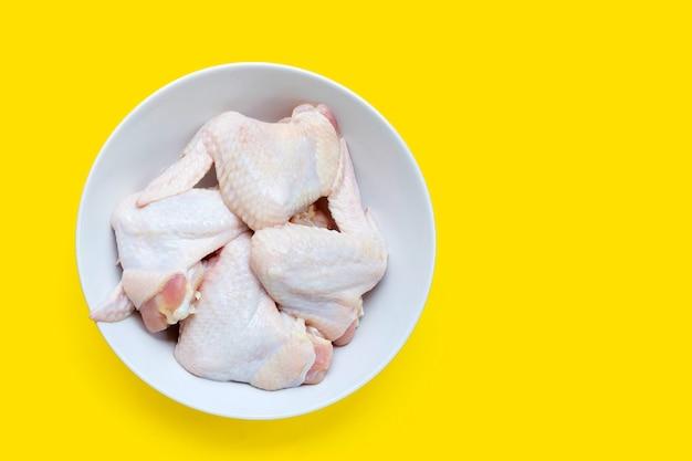 Verse rauwe kippenvleugels in witte kom op gele achtergrond.