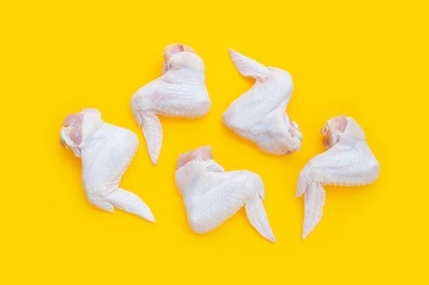 Verse rauwe kippenvleugels op gele achtergrond.