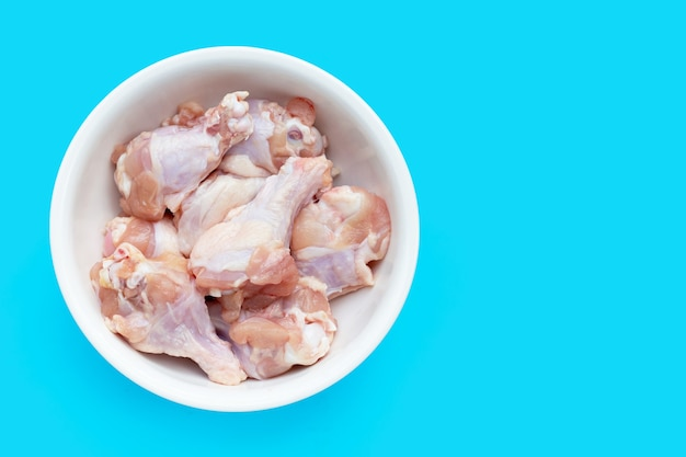 Verse rauwe kippenvleugels (wingstick) in witte kom op blauwe achtergrond.