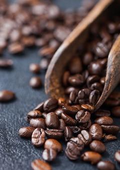 Verse rauwe koffiebonen in houten lepel op zwarte achtergrond. macro
