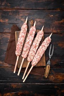 Verse rauwe kofta of lula kebab spiesjes set, op oude donkere houten tafel achtergrond, bovenaanzicht plat lag