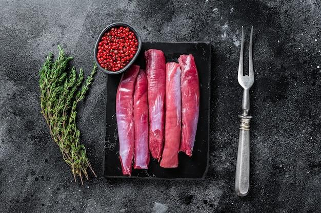 Verse rauwe lamshaasfilet, schapenvlees entrecote op marmeren bord met tijm. zwarte achtergrond. bovenaanzicht.