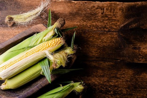 Verse rauwe maïskolven op een donkere houten ondergrond. gezonde voeding, vegetarisme concept. plaats om tekst in te voegen.