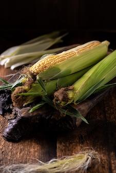 Verse rauwe maïskolven op een houten ondergrond. gezonde voeding, vegetarisme concept.