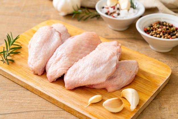 Verse rauwe middelste kippenvleugels op een houten bord