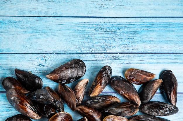 Verse rauwe mosselen op blauwe houten achtergrondkleur