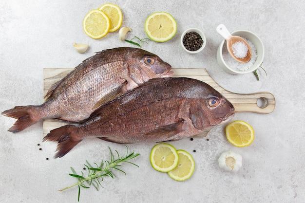 Verse, rauwe ongekookte zee dorado, dorada vis met citroen, rozemarijn, kruiden, specerijen en olijfolie op een houten snijplank.