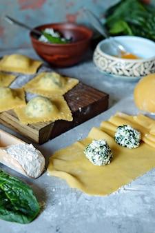 Verse rauwe ravioli met ricotta en spinazie op een blauwe achtergrond.