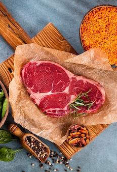 Verse rauwe rib-eye steak op houten snijplank, met spinazie, linzen en rozemarijn in een rustieke stijl.