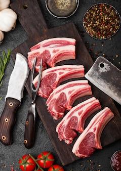 Verse rauwe slagers lam rundvlees koteletten op stenen bord met vintage vlees vork en mes en houthakkersbijl