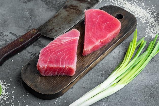 Verse rauwe tonijn steak met doperwt, sesam en lente-uitjes set, op houten snijplank, en oud slagersmes, op grijze steen