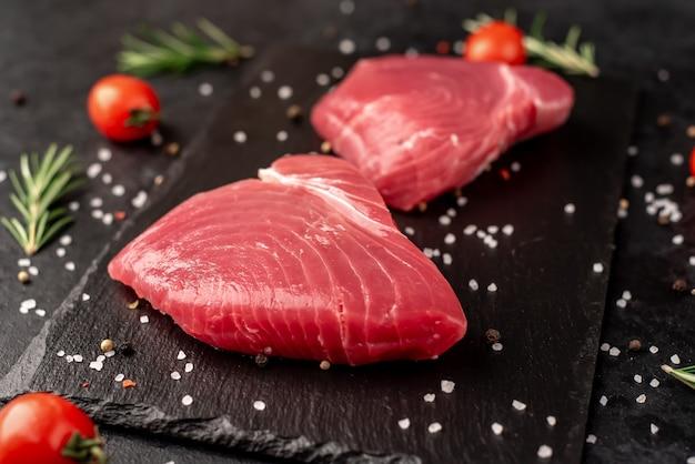 Verse rauwe tonijnlapjes vlees met rozemarijn en kruiden op een stenen achtergrond