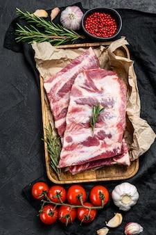 Verse rauwe varkensribbetjes met rozemarijn en knoflook in een houten kom. bovenaanzicht