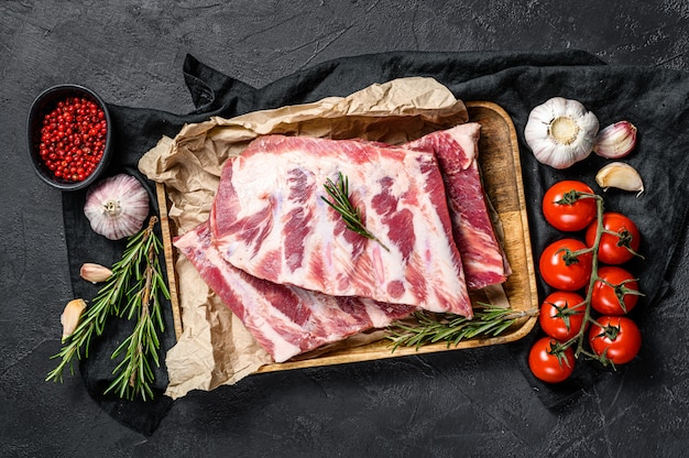 Verse rauwe varkensribbetjes met rozemarijn en knoflook in een houten kom.
