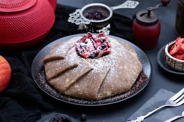 Verse rauwe vegan taart met bessen op een zwart dienblad