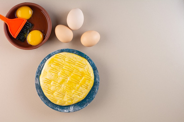 Verse rauwe witte kippeneieren die op beige tafel worden geplaatst.