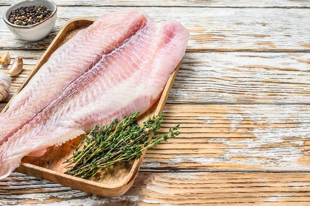 Verse rauwe witte visfilet meerval met kruiden.