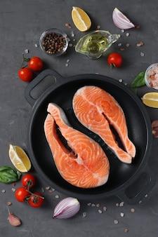 Verse rauwe zalmlapjes vlees in een grillpan en ingrediënten op een donkere achtergrond. uitzicht van boven. verticaal formaat