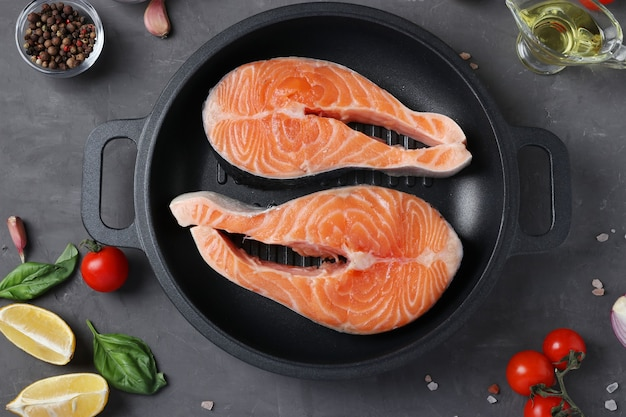 Verse rauwe zalmlapjes vlees in een grillpan en ingrediënten op een donkere achtergrond. uitzicht van boven