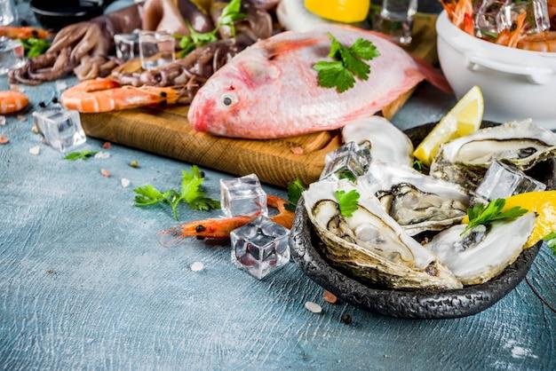 Verse rauwe zeevruchten inktvis garnalen oester mosselen vis met kruiden van kruiden